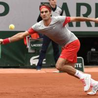 Easy does it: Roger Federer attempts to hit a return against Lukas Lacko during their first-round match at the French Open on Sunday. Federer won 6-2. 6-4, 6-2. | AFP-JIJI