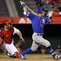 Unorthodox swing: Kansas City's Norichika Aoki strokes an RBI single in the 13th inning against Los Angeles on Saturday night. The Royals beat the Angels 7-4. | AP