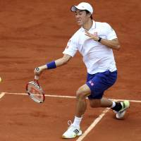 One and done: Kei Nishikori plays a shot from Slovakia's Martin Klizan in their first-round match at the French Open on Monday. | AP