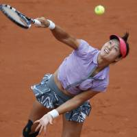 Own worst enemy: Li Na serves during her 7-5, 3-6, 6-1 loss to France's Kristina Mladenovic in the first round of the French Open on Tuesday. | REUTERS