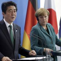Prime Minister Shinzo Abe (left) and German Chancellor Angela Merkel address the media during a joint press conference as part of a meeting at the chancellery in Berlin on Wednesday. | AP