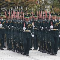 Members of a Self-Defense Forces honor guard march as they prepare to be inspected by U.S. Secretary of Defense Chuck Hagel at the Defense Ministry in Tokyo on April 6. | AP