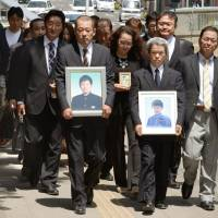 Plaintiffs who lost their children to tsunami at Okawa Elementary School in Ishinomaki, Miyagi Prefecture, head for the Sendai District Court on Monday as legal proceedings began in their lawsuit against the city and the prefecture. | KYODO