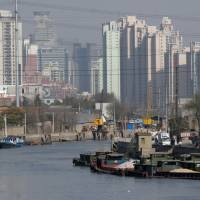 Barges filled with construction materials are docked at Suzhou Creek in Shanghai. | BLOOMBERG