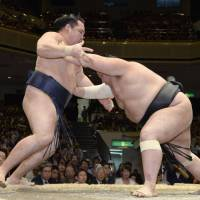 In a tough position: Komusubi Chiyootori sends yokozuna Kakuryu backpedaling on Saturday at the Summer Grand Sumo Tournament. | KYODO