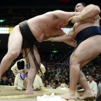 Get out of here: Hakuho defeats Kakuryu in a battle of yokozuna on Saturday. | KYODO