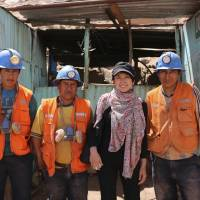 Natsuko Shiraki poses with workers at a gold mine in Peru in November 2013. | COURTESY OF NATSUKO SHIRAKI