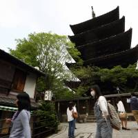Tourists mill about in front of a five-story pagoda at a temple in Kyoto at the beginning of this month. | BLOOMBERG