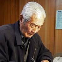 Hiratsuka, who has been on the job for 65 years, works in his office, writing another story about local residents. | AFP-JIJI