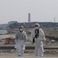 Decked out in full hazmat suits, Kazuhiro Onuki (right) and his wife, Michiko, take a stroll along the coast during a return trip to their hometown of Tomioka on April 17 as the Fukushima No. 2 nuclear plant, located south of the crippled Fukushima No. 1 complex, looms in the background.  | AP