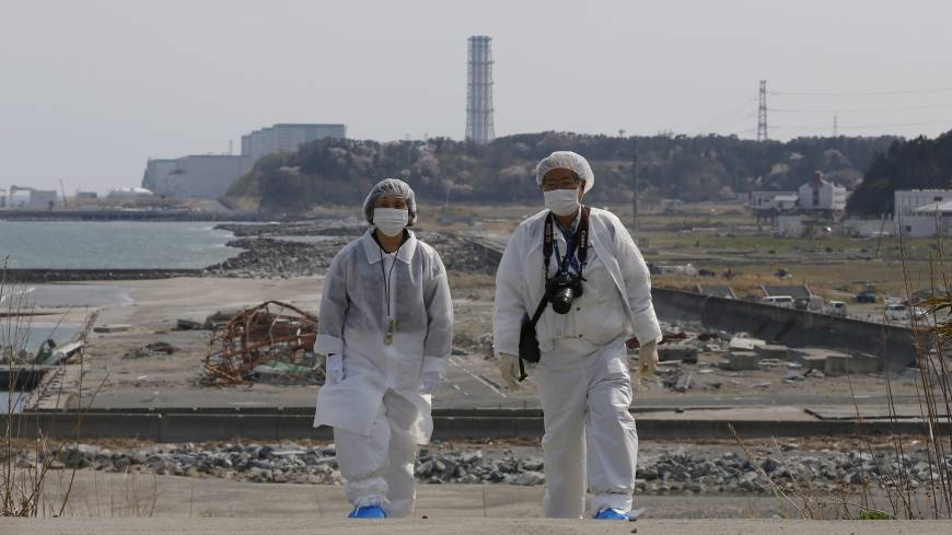 Decked out in full hazmat suits, Kazuhiro Onuki (right) and his wife, Michiko, take a stroll along the coast during a return trip to their hometown of Tomioka on April 17 as the Fukushima No. 2 nuclear plant, located south of the crippled Fukushima No. 1 complex, looms in the background.