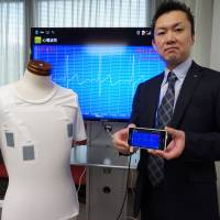 Hiroshi Koizumi, who heads the life-care devices research group at NTT Microsystem Integration Laboratories, shows off a hitoe shirt that can measure heart rates and take electrocardiograms, in Tokyo on April 14. | KAZUAKI NAGATA