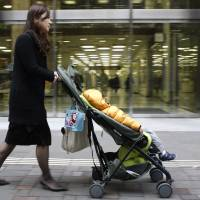 Yoko Furukawa, an employee of Nippon Yusen K.K., pushes a baby stroller during her morning commute in the Marunouchi district of Tokyo. | BLOOMBERG