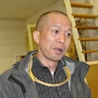 He Yunchang wears one of his ribs as a necklace in Beijing on April 18. | AFP-JIJI