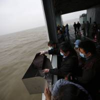A man scatters the ashes of his parents and grandmother into the ocean during a burial ceremony off Shanghai on May 10. Faced with an aging population, soaring property prices and increasingly scarce land, the Chinese government has been trying for years to convince more people to break with tradition and bury loved ones at sea. | REUTERS