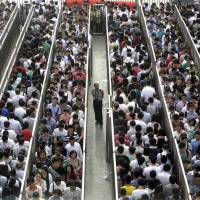 Passengers await a security check at Beijing's Tiantongyuan North Station during morning rush hour Tuesday. Beijing tightened checks at subway stations after a deadly attack last week in the Xinjiang region. | REUTERS