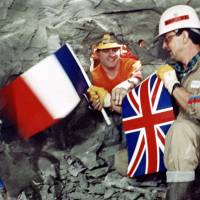 Tunnel workers Philippe Cozette from France (right) and Graham Fagg from England (left) shake hands while holding national flags during the breakthrough in the construction of the Channel Tunnel on Dec. 1, 1990. | AFP-JIJI