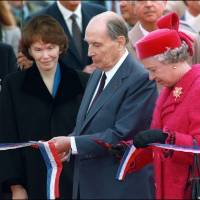 French President Francois Mitterrand and Britain's Queen Elizabeth II cut a ribbon as Mitterrand's wife, Danielle, looks on at the inauguration of the Channel Tunnel in Coquelles, a commune in the French department of Pas-de-Calais, on May 6, 1994. | AFP-JIJI