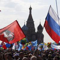 People wave flags and banners during a May Day rally held in Moscow's Red Square on Thursday. | REUTERS