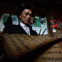 Chinese shaman Zhao Fucheng thumbs through an ancient text that is said to predict the future, at his home in the village of Qiuka in Guangxi province. | AFP-JIJI