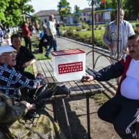 People sit near an empty ballot box on Sunday in the eastern Ukrainian town of Svatove. As thousands turned out for rebel-held independence referendums across the country's east, Svatove stood out as a brave refusnik — apparently the only one in the region. | AFP-JIJI
