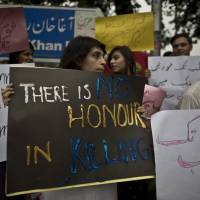 A protester in Islamabad holds a sign Thursday reading, 'There is no honor in killing,' after a woman was stoned to death in Lahore. | AP