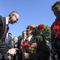 Prime Minister Arseniy Yatsenyuk shakes hands with Ukrainian veterans in Kiev on Friday during a ceremony marking Victory Day, commemorating the defeat of Nazi Germany. | AFP-JIJI