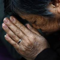 A woman prays during a weekend Mass at the church, which is barely tolerated by the Communist Party. | REUTERS