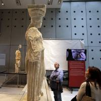 Visitors look at caryatids on show at the Acropolis museum in Athens while a monitor behind  relays the cleaning operation of another caryatid. | AP