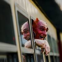 A man in devil makeup looks out of a railway car as he travels through the Harz mountains to celebrate the Walpurgisnacht pagan festival on Wednesday. | REUTERS