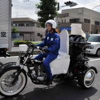 A rider demonstrates Japanese toilet goods-maker Toto's eco-friendly Toilet Bike Neo motorcycle, which uses bio-gas from livestock or waste water discharges, as part of the firm's green campaign in Omiya, western Tokyo, in August 2012. | AFP-JIJI