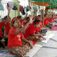 Land-grab victims from Michaung Kan in eastern Yangon stage a sit-in at their protest camp in front of City Hall on April 28. | AP