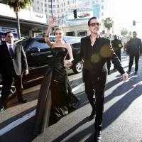 Angelina Jolie waves at fans as she arrives with Brad Pitt at the premiere Wednesday of the Disney fantasy adventure film 'Maleficent,' starring Jolie, at El Capitan Theatre in Hollywood. | REUTERS
