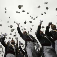 Graduates toss their hats in the air at the end of a commencement ceremony at the U.S. Military Academy at West Point, New York, on Wednesday. President Barack Obama's address at the event was the first in a series of speeches that he will use to explain the future course of his administration's foreign policy. | REUTERS