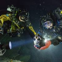 Divers recover a skull from an underwater cave on Mexico's Yucatan Peninsula in June 2013. A remarkable 12,000-year-old skeleton found in the cave in 2007 provides a crucial link on the ancestry of modern Native Americans, scientists said Thursday. | REUTERS