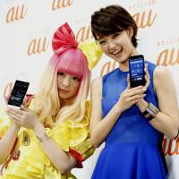 Singer Kyary Pamyu Pamyu (left) and actress Ayame Goriki hold KDDI smartphones during a promotional event in Tokyo last May. British researchers are launching a major study to investigate whether using wireless gadgets might affect brain development. | KYODO