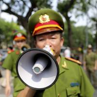 A Vietnamese police officer orders passers-by to vacate an area near the Chinese Embassy in Hanoi on Sunday as authorities forcibly broke up anti-China protests. | AP