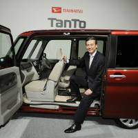 Daihatsu Motor Co. President Masanori Mitsui shows off an updated version of the Tanto minicar in Tokyo in October. | KYODO