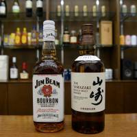 Bottles of Jim Beam bourbon and Suntory's Yamazaki whisky are displayed at Suntory's office in Tokyo in January. | AFP-JIJI