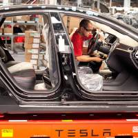 A Model S sedan makes its way along an assembly line at Tesla's plant in Fremont, California, last July. | BLOOMBERG