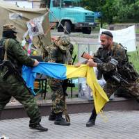 Pro-Russian fighters from the Vostok Battalion tear apart a Ukrainian flag outside a state building in the eastern Ukrainian city of Donetsk on Thursday. | AFP-JIJI