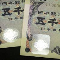 The next version of the ¥5,000 bill (right) is displayed with the current version in Tokyo on Thursday. The bigger and square-shaped hologram sticker with a different texture is aimed at making the bill easier to recognize by visually impaired people, who are becoming a growing segment of Japan's rapidly graying population. The government will start issuing the new banknote Monday.   BLOOMBERG