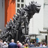 A 6-meter-tall statue of Godzilla towers over visitors after it was unveiled in front of the TCL Chinese Theatre in Hollywood, California, on May 9, ahead of the release of the latest Hollywood reboot of the classic monster movie. | AFP-JIJI