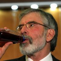Sinn Fein leader Gerry Adams takes a drink before a news conference in Belfast on Sunday following his release from Antrim police station, where he was detained for questioning over a 1972 murder. | AFP-JIJI