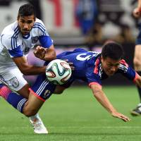 Pick up the pace: Yasuyuki Konno (right) competes for the ball with Cyprus' Nestor Mytidis during Japan's 1-0 friendly win in Saitama on Monday night. | AFP-JIJI