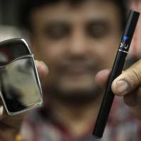 A sales clerk displays a Zippo Blu butane lighter and a Blu e-cigarette at a store in Brookline, Massachusetts, on Wednesday. | AP