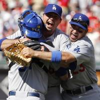 No doubt about it: Dodgers pitcher Josh Beckett (center) is hugged by first baseman Adrian Gonzalez (right) and catcher Drew Butera after throwing a no-hitter against the Phillies on Sunday afternoon. | AP