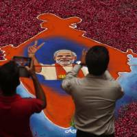 Indians take photographs of a portrait of Bharatiya Janata Party leader Narendra Modi made with colored powder and surrounded by rose petals at the party offices in Gandhinagar, in the western Indian state of Gujarat, on Friday. | AP