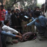 Police collect evidence near the body of Farzana Iqbal after she was stoned to death outside the Lahore High Court on Tuesday. Iqbal had been waiting for the court to open when around a dozen family members attacked her with bricks. | REUTERS