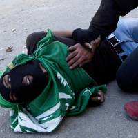 A man tries to aid Palestinian Mohammad Abu Daher, 17, moments after he was shot in a clash with Israeli troops near the West Bank city of Ramallah on Thursday. | AP